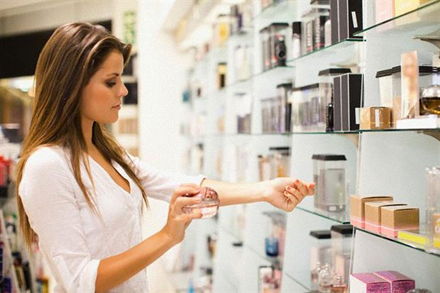 woman smelling perfume in a shop